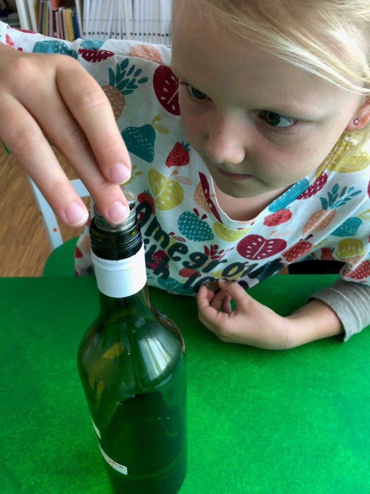 Münzen auf den Flaschenhals stapeln zur Steigerung der Fingerfertigkeit